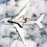 The Buran space shuttle mounted on a transport plane in flight.