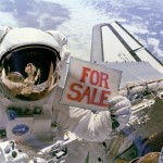 "Astronaut Dale A. Gardner, having just completed the major portion of his second extravehicular activity (EVA) period in three days, holds up a ""For Sale"" sign."