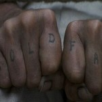 Two fists with the words Hold Fast tattooed on the fingers.