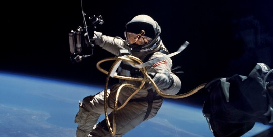 An astronaut in space with Earth below and connected by an umbilical.