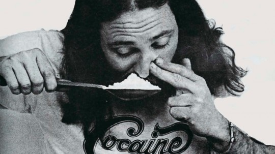 A hippy snorting a big spoon of cocaine