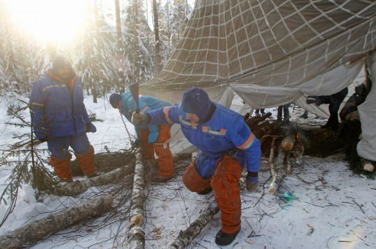 Astronauts and cosmonauts chopping wood for a fire.