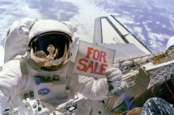 A NASA astronaut holds up a For Sale sign over a satellite about to be deployed.